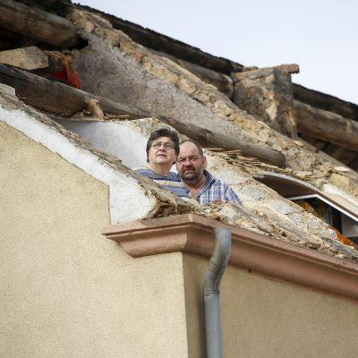 Mies ja nainen katselevat kattoon syntyneestä aukosta.