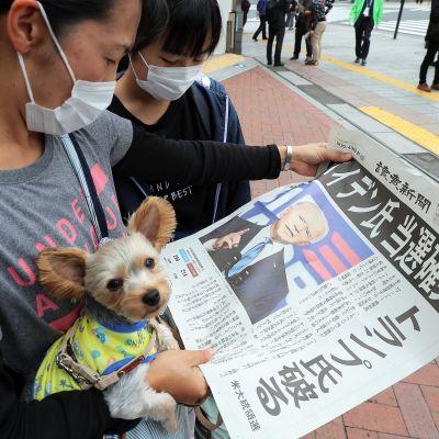 Kaksi ihmistä lukee sanomalehteä kadulla Tokiossa.