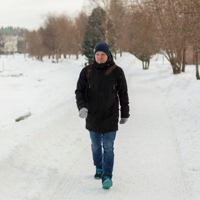 Mies kävelee lumisessa maisemassa joen varrella.