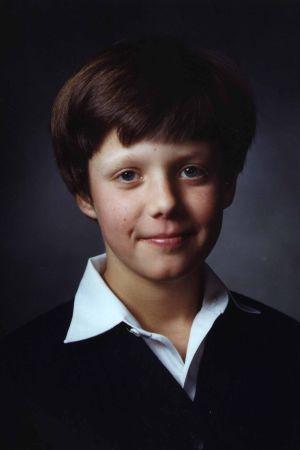 Ung pojke i vit kraskjorta och mörk pullover