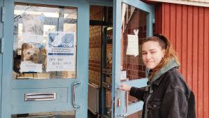 En ung kvinna öppnar en dörr. Till vänster synns en plansch där det framkommer att det här är en vallokal i Boxby skola.
