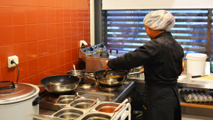 En kvinna i mörka kock-kläder står och rör om i en stekpanna.