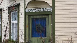 En ingång till ett ljusgult trähus med gröna kanter. Ovanför dörren står det Kellola 1880.