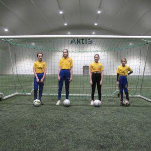 Fyra flickor står på rad vid ett fotbollsmål.