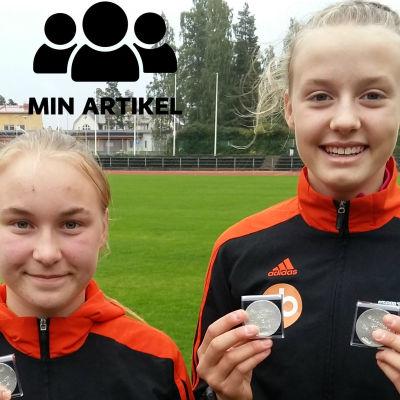 Två flickor med silvermedaljer i händerna. De är klädda i svart-orangefärgade.