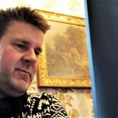 En medelåldersmans ansikte, han tittar på en datorskärm. I bakgrunden syns en tavla på väggen.