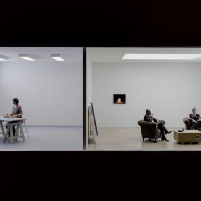 Kuvataiteilijan teos, jossa näkymä kahteen huoneeseen, joissa ihmiset puuhissaan