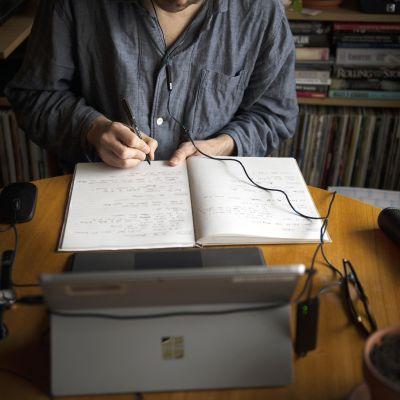 Pyjamaan pukeutunut mies työskentelee kotonaan.
