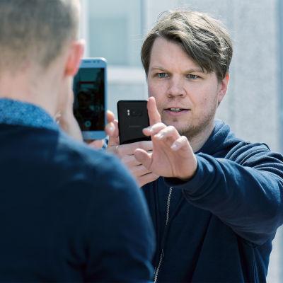 Lyhytelokuvan näyttelijä Hannes Suominen kuvaa kännykällä töistä miestä, joka on hänen edessään kuvaamassa kännykällä.