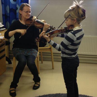 elev övar violinspelande med sin lärare