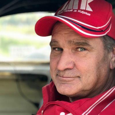 Mies katsoo auton ikkunasta kohti kameraa punainen lippalakki päässään
