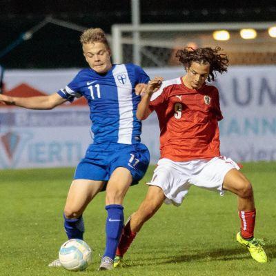 Pyry Hannola och en österrikisk spelare i en duell i en juniorlandslagsmatch.