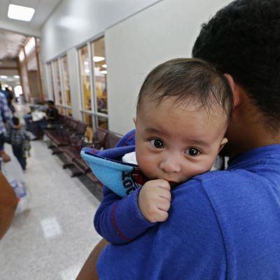 Murrosikäinen poika kantaa pientä vauvaa jonossa.
