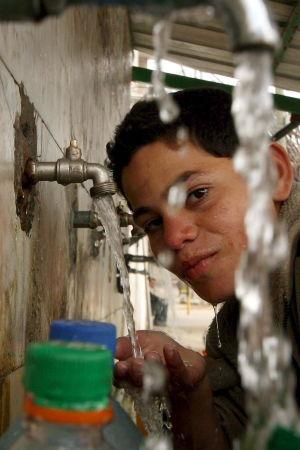 Palestinsk pojke fyller vattenkanistrar på flyktingläger i södra Gaza
