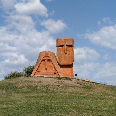 En skulptur föreställande en stiliserad man och kvinna uppe på en kulle.