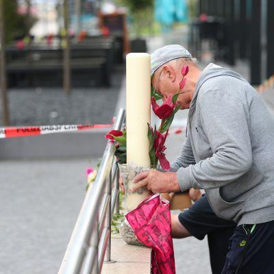 Mies toi kynttilän Olympia-ostoskeskuksen läheiselle metroasemalle lauantaiaamuna Münchenissä.