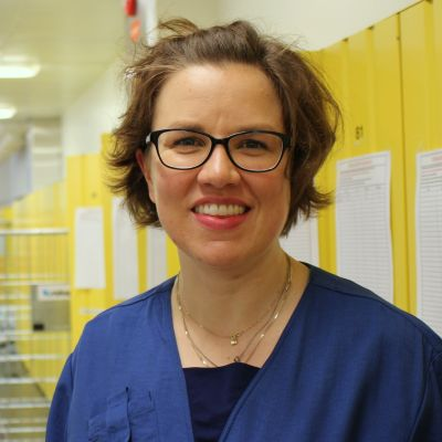 Sairaanhoitaja Riitta Mertanen sairaalan pukukaapeilla