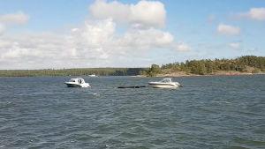 En brygga flyter på havet med en båt på släp.
