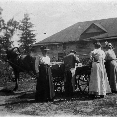 Gårdfarihandlande med häst. Tre okända kvinnor. Uthus i bakgrunden.