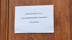 En papperslapp upphängd på en trädörr. På lappen står det: Andakt med lunch serveras i finska församlingshemmet, Lundagatan 5. Välkommen.