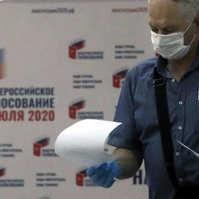 Mies maski kasvoillaan äänestyslippu kädessään.