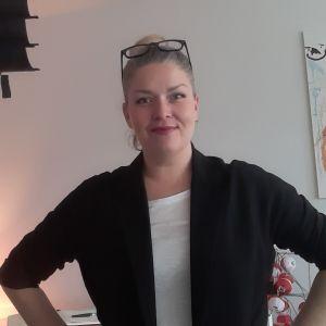 en kvinna som står inomus i ett vitt vardagsrum
