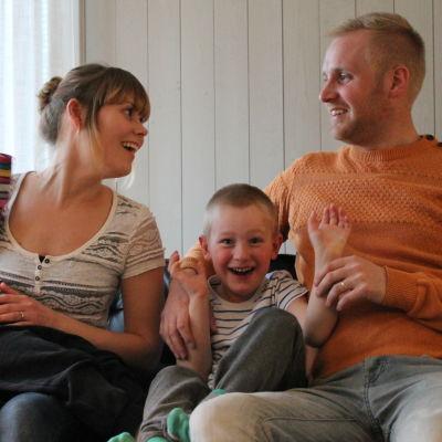 Tanja och Mathias Forsblom sitter med barnen i soffan.