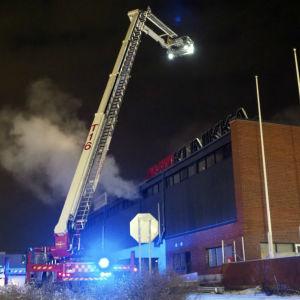 Brandkårens kran utanför en rykande byggnad.