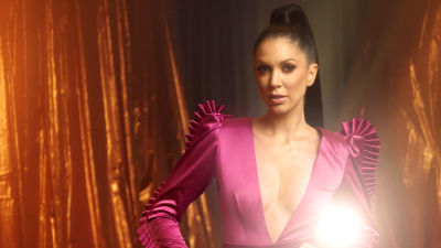 UMK-kilpailija Laura poseeraa kädet lanteilla kultaisin verhoin vuoratussa huoneessa. Päällä on aniliininpunainen kireä housupuku.