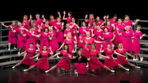 Många kvinnor klädda i ljusröda klänningar poserar mot svart bakgrund.