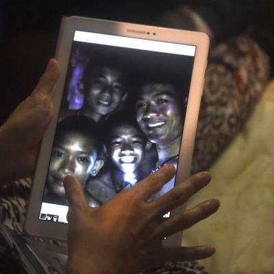Omaiset katsoivat Tham Luangin luostastosta löytyneiden hengissä olevien lastensa kuvia näytöltä 2. heinäkuuta.