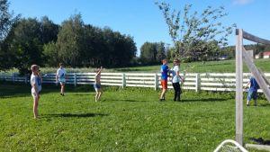 Pojkar på gräsmatta som spelar fotboll på gården hemma.