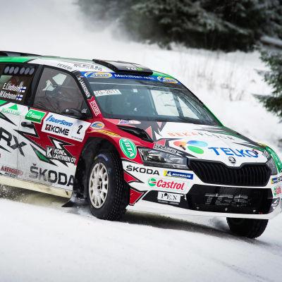En rallybil susar fram på en snötäckt väg.
