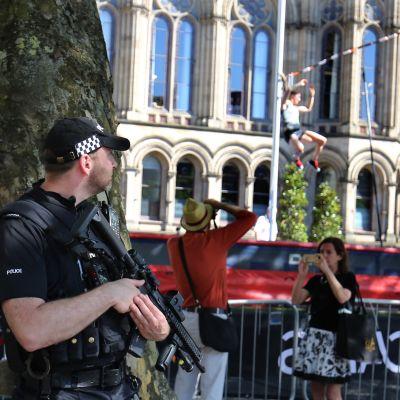 Aseistettu poliisi seisoo kadulla. Taustalla mies jottaa valokuvaa seivästä hyppäävästä toisesta miehestä. Nainen ottaa kuvaa toiseen suuntaan.