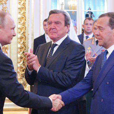 Vladimir Putin kättelee  Dmitri Medvedeviä.