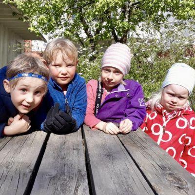 Fyra barn i dagisåldern vid ett bord utomhus.