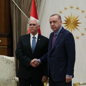 Yhdysvaltain varapresidentti Mike Pence ja Turkin presidentti Racip Tayyip Erdoğan kättelevät ja poseeraavat kameralle.