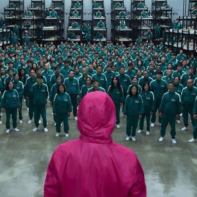 Punahuppuinen hahmo johtaa ihmisryhmää.