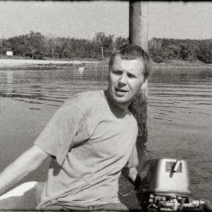 Nuori, t-paitaan pukeutunut mies istuu veneen takaosassa ja ohjaa perämoottoria. Taustalla näkyy meri ja tyhjä ranta.