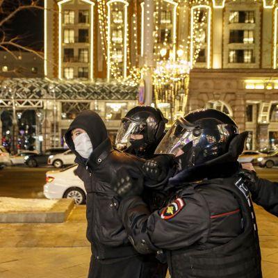 Mellakkavarusteisiin pukeutuneet poliisit taluttavat mielenosoittajaa Moskovassa.