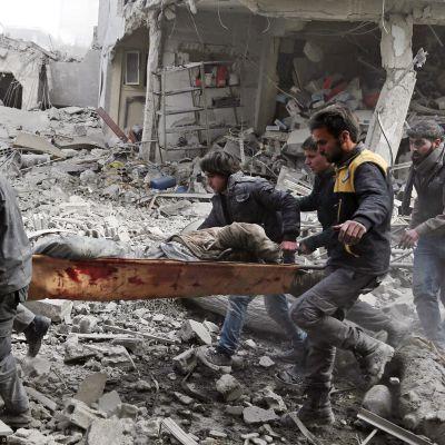 Syyrialaiset kantavat pommituksissa tuhoutuneen talon raunioista pelastettua  Itä-Ghoutan Saqbassa.
