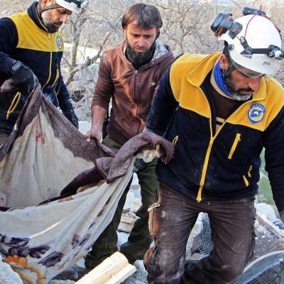 Syyrian siviilipuolustuksen jäsenet kantavat ilmaiskussa kuolleiden ruumiita raunioista Maaret Misrinissä Idlibissä.