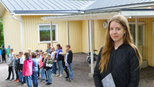 En flicka står framför ett gult hus och ser in i kameran. Bakom henne syns andra lågstadiebarn.