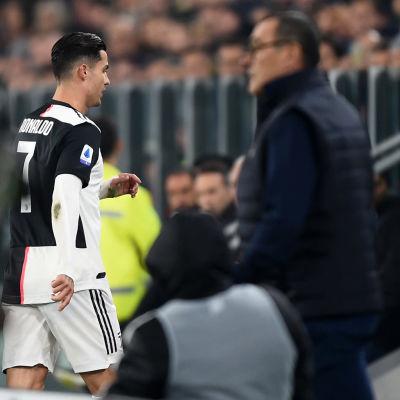 Cristiano Ronaldo vandrar bort från planen bredvid Maurizio Sarri.