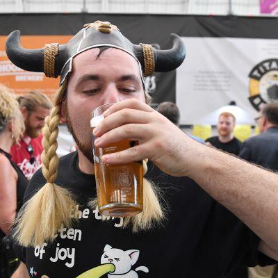 Sarvihattuinen mies juo olutta olutfestivaaleilla Lontoossa.