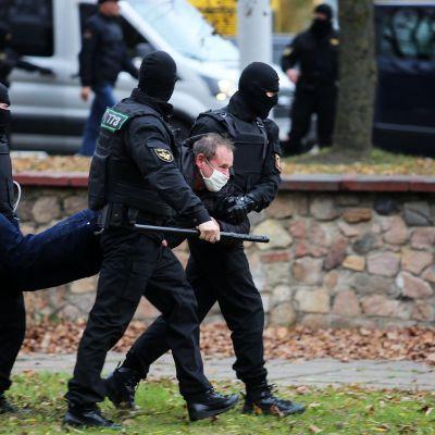 Mellakkapoliisit kantavat miestä mielenosoituksen yhteydessä Minskissä.