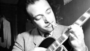 Django Reinhardt näppäilee kitaraa tupakka suussa, mustavalkoisessa kuvassa