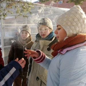 Sarjan Nollatoleranssi nuoret tupakoivat ringissä. Poika ojentaa tytölle tupakan.
