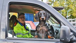En svart och brun tax står och tittar ut genom ett bilfönster. Inne i bilen sitter en man i gul jacka och ler.