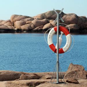 En röd- och vitrandig livboj hänger på en stolpe på en klippa med hav i bakgrunden.